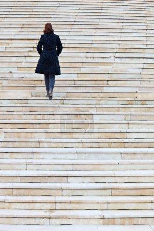 Photo pour Femme solitaire qui marche escalier - image libre de droit