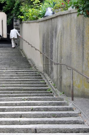An old anonymous man ascending the stairs in an old swiss town