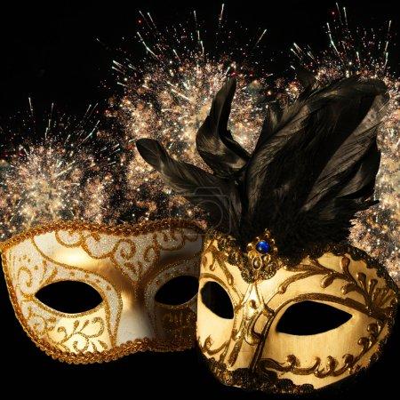 Ornate carnival masks on firework background