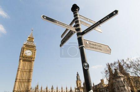 Photo pour Tir faible angle de big ben à Londres, avec des directions de signer à l'avant-plan pointant vers les attractions touristiques autour de la zone. - image libre de droit