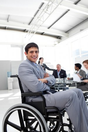 Attractive businessman sitting in a wheelchair with folded arms