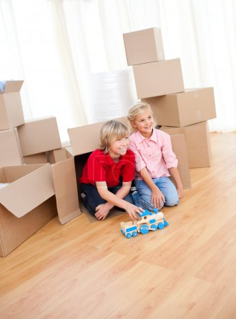 Smiling sibling playing while moving house