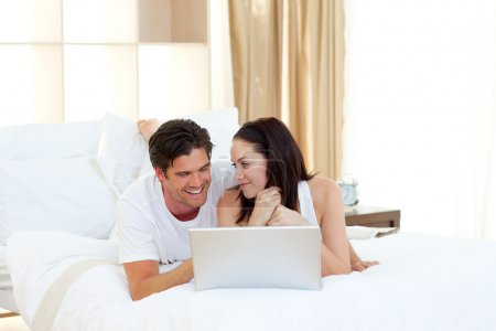 Young couple using a laptop lying on their bed