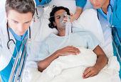 Lékaři nesoucí pacienta na jednotce intenzivní péče