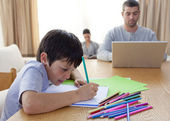 Chlapec malování a rodiče pracující doma