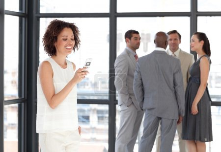 Smiling businesswoman on phone in office with her team