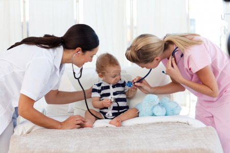 Nurse and pediatrician attending to a baby