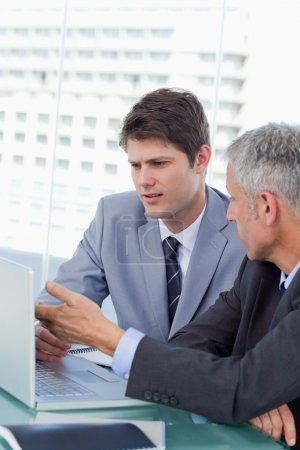 Portrait of businessmen working with a laptop