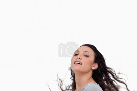 Sensual looking young woman flipping her hair