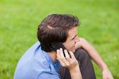 Mladý usmívající se muž mluví po telefonu při posezení v parku
