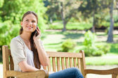 Smiling woman on her cellphone while sitting on a park bench