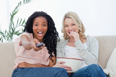 Two women looking at the camera holding popcorn and a television