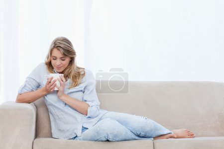 A woman is smelling a cup of coffee that she is holding