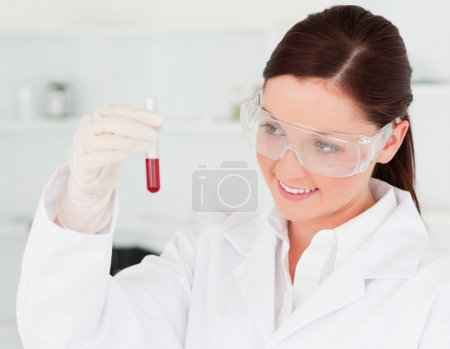 Pretty scientist looking at a test tube in a lab