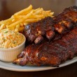 Pork ribs back with french fries and coleslaw sala...