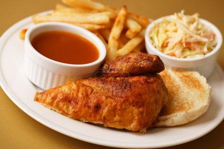 Photo pour Poitrine de poulet rôtie avec frites, salade de salade de salade de chou et sauce barbecue sur le côté. Profondeur de champ faible . - image libre de droit