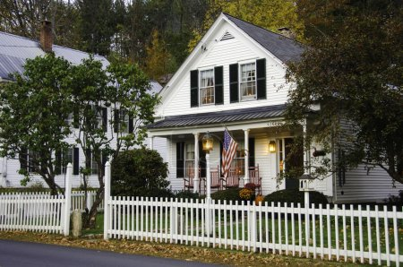 Photo for White clapboard house with a white picket fence - Royalty Free Image