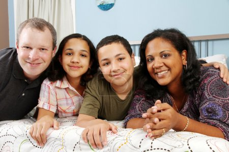 Photo for Family laying down together in a bed - Royalty Free Image