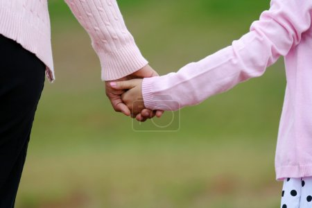 Photo for Mother and daughter holding hands while walking together - Royalty Free Image