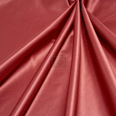 Folds of glossy smooth red satin fabric.
