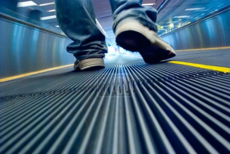 Foot walking in airport escalator perspective view (ground level)