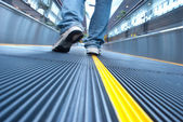 Man walking in airport escalator perspective view (ground level)