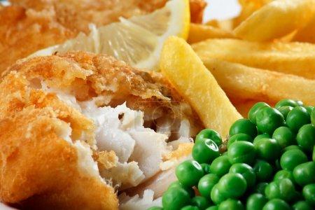 Photo pour Gros plan de fish and chips avec des petits pois et une tranche de citron. Un plat traditionnel britannique au bord de la mer - image libre de droit