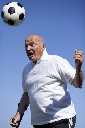 A senior football player with walking stick to head a soccerball