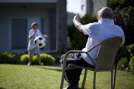 Photo pour Vieillard avec canne assis sur la chaise et l'enseignement de football jouant à son adorable petit-fils - image libre de droit