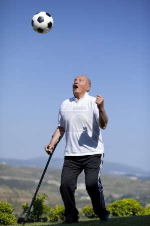 Retired football player with walking stick to head a soccerball
