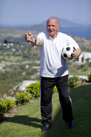 Retired football player with walking stick holding a soccerball