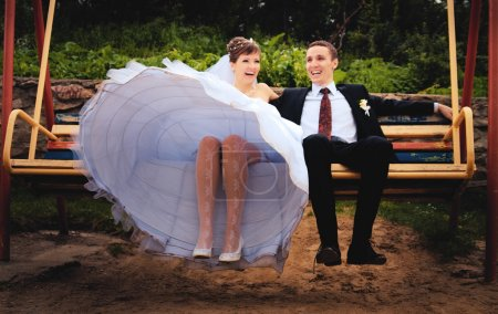 Bride and groom swing on a swing