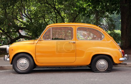 Photo for Side view of old small yellow car with flat tire. - Royalty Free Image