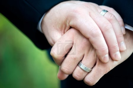 Photo for This image shows two men holding hand displaying their wedding rings. - Royalty Free Image