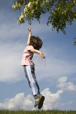 Jump of little girl and tree in the spring