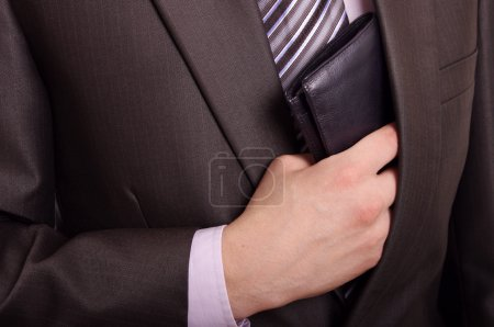 A suited man taking out his black leather wallet