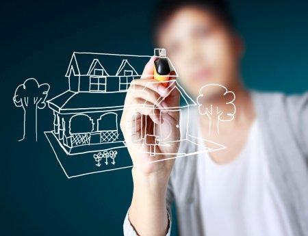 Photo pour Main, dessin de maison dans un tableau blanc - image libre de droit