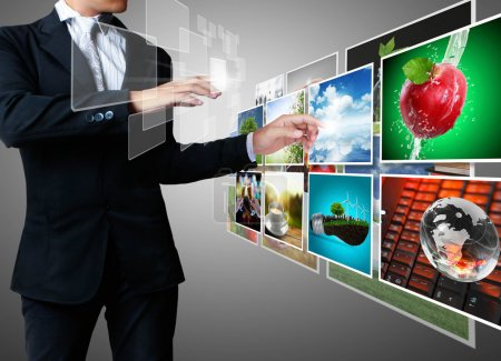 Photo for Hand pushing images streaming touch screen interface - Royalty Free Image