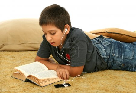 Boy studing laying down and listening with a mp4 p...