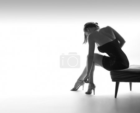 Photo for A slim, young woman sets her high heel shoes - Royalty Free Image