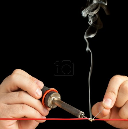 Photo for Soldering Tech soldering a red wire isolated on a pure black background. - Royalty Free Image