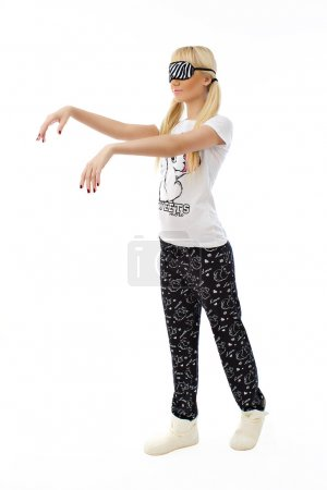 Sleepwalking blonde girl in pajamas on white background