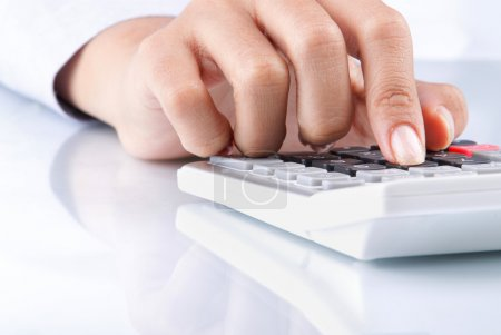 Photo for Close up of hand using calculator on white background - Royalty Free Image