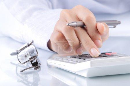 Photo pour Les mains de la femme avec une calculatrice et un stylo. journal sur fond - image libre de droit