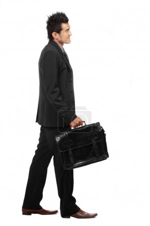 A young businessman is walking