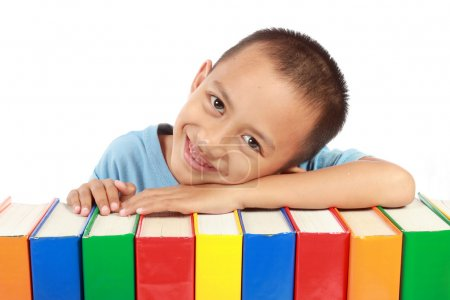 Portrait of young boy leaning on top of his colorful books