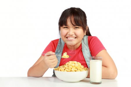 Portrait of smiling young girl having breakfast against white