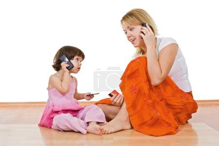 Photo pour Jeune belle femme parlant au téléphone et tenant dans sa main une carte bancaire et la petite fille l'imitent - image libre de droit