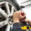Close Up of hands of mechanic changing wheel of a limousine, with blurred background of garage.