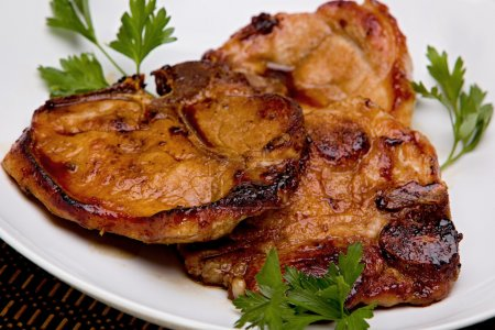 Photo pour Gros plan de porc caramélisé côtelettes sur une plaque blanche. - image libre de droit